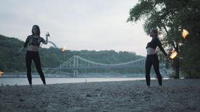 Zwei junge Frauen, die eine Show mit den Flammenbällen stehen auf dem Riverbank durchführen Talentiertes fireshow weibliches Küns stock video