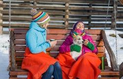Zwei junge Frauen, die in einem hölzernen Schaukelstuhl auf einem kühlen w sich entspannen lizenzfreies stockbild