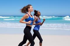 Zwei junge Frauen, die entlang den Strand laufen Stockfoto