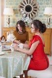 Zwei junge Frauen, die Frühstück am Küchentisch essen Lizenzfreie Stockfotos