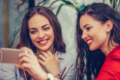 Zwei junge Frauen, die Handy und das Lächeln betrachten stockfotografie