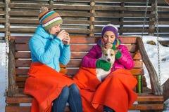 Zwei junge Frauen, die an an heißem Kaffee in einem hölzernen Schaukelstuhl nippen stockbilder