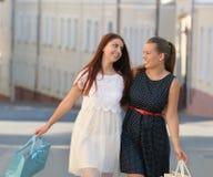 Zwei junge Frauen, die hinunter die Straße mit Einkaufstaschen gehen Lizenzfreie Stockbilder