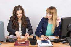 Zwei junge Frauen, die im Büro arbeiten, man setzt ein Blatt Papier, das zweite in der Verwunderung, die entlang sie anstarrt Lizenzfreies Stockbild