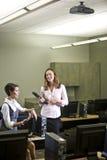 Zwei junge Frauen, die im Computerlabor sich unterhalten Stockbilder