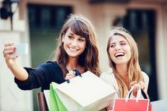 Zwei junge Frauen, die im Einkaufszentrum kaufen, ein selfie nehmend Stockbilder