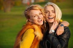 Zwei junge Frauen, die im Park lachen Lizenzfreie Stockbilder