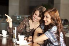 Zwei junge Frauen, die Kaffee an einem Stab trinken Stockbild