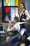 Zwei junge Frauen, die Laptope am Tisch treffen Stockbilder