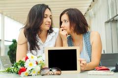 Zwei junge Frauen, die leere Tafel mit Holzrahmen in Ca halten lizenzfreie stockfotografie