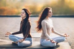 Zwei junge Frauen, die in Lotus Pose auf dem Dach im Freien meditieren Lizenzfreies Stockfoto
