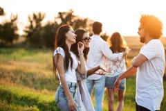 Zwei junge Frauen, die mit dem jungen gelockten Mann im Freien plaudern Im Hintergrund umfasst ein junger Mann ein Mädchen lizenzfreie stockfotografie