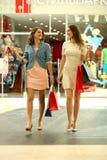 Zwei junge Frauen, die mit im Geschäft kaufen gehen Lizenzfreie Stockfotografie