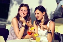Zwei junge Frauen, die mit kalten Getränken zujubeln lizenzfreies stockfoto