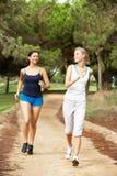 Zwei junge Frauen, die in Park laufen Stockfoto