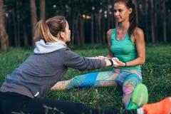 Zwei junge Frauen, die Partneryoga durchführen, werfen, doppelter Sitzstraddle auf und dehnen ihr Bein und Rückenmuskulatur aus,  lizenzfreies stockfoto