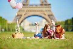 Zwei junge Frauen, die Picknick nahe dem Eiffelturm in Paris, Frankreich haben lizenzfreie stockfotos