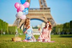 Zwei junge Frauen, die Picknick nahe dem Eiffelturm in Paris, Frankreich haben lizenzfreie stockfotografie