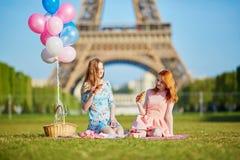 Zwei junge Frauen, die Picknick nahe dem Eiffelturm in Paris, Frankreich haben lizenzfreies stockbild