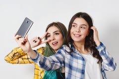 Zwei junge Frauen, die selfie mit Handy nehmen Auf Weiß lizenzfreie stockfotos