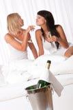 Zwei junge Frauen, die Spaß im Luxushotelraum haben Lizenzfreies Stockbild