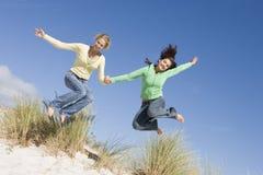 Zwei junge Frauen, die Spaß am Strand haben Stockfotografie