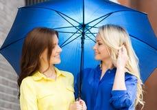 Zwei junge Frauen, die unter einem Regenschirm aufwerfen Stockfotografie