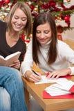 Zwei junge Frauen, die Weihnachtskarten schreiben Lizenzfreie Stockfotografie