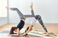 Zwei junge Frauen, die Yoga asana abwärtsgerichteten Hund tun Lizenzfreie Stockfotos