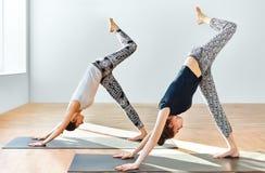 Zwei junge Frauen, die Yoga asana abwärtsgerichteten Hund tun Stockfoto
