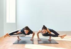 Zwei junge Frauen, die Yoga asana Achtwinkelhaltung tun Stockfoto