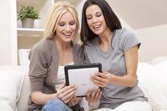 Zwei junge Frauen, die zu Hause Tablette-Computer verwenden Stockfotografie