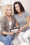 Zwei junge Frauen, die zu Hause Tablette-Computer verwenden Stockbild
