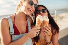 Zwei junge Frauen, die zusammen eine Eiscreme essen Stockfotografie