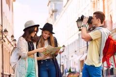 Zwei junge Frauen halten Stadtplan und Kerl mit Kamera Lizenzfreie Stockfotos
