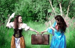 Zwei junge Frauen im Streit weil alter Koffer Stockbilder