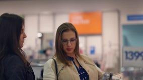 Zwei junge Frauen kaufen im Geschäft, warme Kleidung wählend stock video