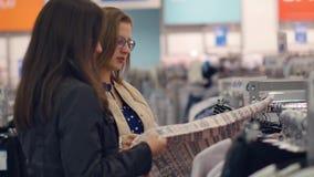 Zwei junge Frauen kaufen im Geschäft, warme Kleidung wählend stock footage