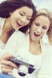 Zwei junge Frauen-Mädchen, die Digitalkamera verwenden Stockfoto