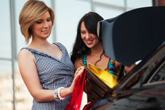 Zwei junge Frauen mit Beuteln eines Einkaufens. Stockbilder