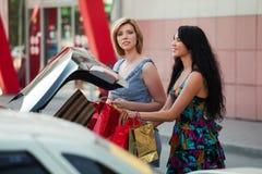 Zwei junge Frauen mit Beuteln eines Einkaufens. Stockfotos