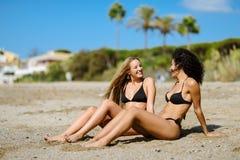 Zwei junge Frauen mit schönen Körpern in der Badebekleidung auf einem tropischen Stockfotos