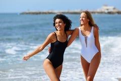 Zwei junge Frauen mit schönen Körpern im Badeanzug auf einem tropischen Lizenzfreies Stockfoto