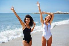 Zwei junge Frauen mit schönen Körpern im Badeanzug auf einem tropischen Lizenzfreies Stockbild