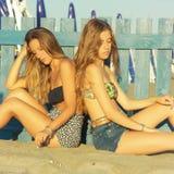 Zwei junge Frauen nach dem Kampf, der auf dem Strand unglücklich sitzt lizenzfreies stockbild