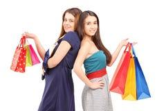 Zwei junge Frauen nach der kaufenaufstellung mit Taschen Stockbild