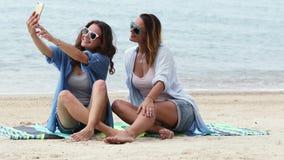 Zwei junge Frauen nehmen ein selfie mit einem Telefon auf dem Strand an einem sonnigen Tag stock footage