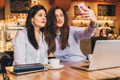 Zwei junge Frauen sitzen in einem Café an einem Tisch vor einem Laptop und tun selfie auf einem Smartphone Treffen von zwei Freun Lizenzfreie Stockfotografie