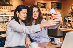 Zwei junge Frauen sitzen in einem Café an einem Tisch vor einem Laptop und tun selfie auf einem Smartphone Treffen von zwei Freun Stockbild