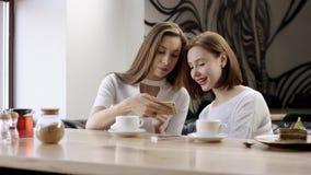 Zwei junge Frauen sitzen in einem Café und in einem Plaudern Es ist eine Freundsitzung Mädchen sitzen im Café am Tisch stock video footage
